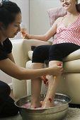 Hispanic woman receiving spa pedicure