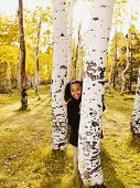 African girl standing behind tree
