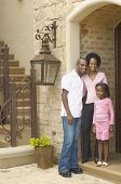 Young African parents with daughter in entrance of house