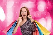 Shopping concept. Beautiful young woman with shopping bags on bright background