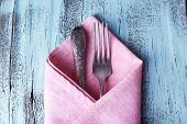 Tableware wrapped in lilac napkin on blue wooden background