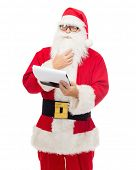 christmas, holidays and people concept - man in costume of santa claus with notepad