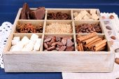 Wooden box with set of coffee and cocoa beans, sugar cubes, dark chocolate, cinnamon and anise on wo