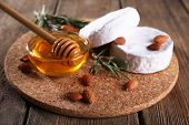 Camembert cheese, honey in glass bowl and nuts on wooden background