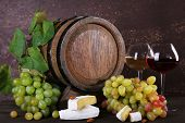 Wine in goblets, Camembert and brie cheese, grapes and wooden barrel on wooden table on wooden background