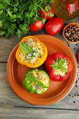 Composition with stuffed peppers on plate and fresh herbs, spices and vegetables, on wooden backgrou