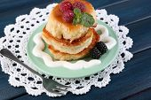 Tasty pancakes with fresh berries and mint leaf on plate, on color wooden background
