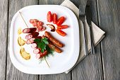Assortment of tasty thin sausages on plate, on wooden background