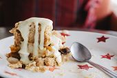 Slice of freshly baked apple crumble with cream