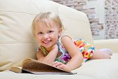 Little girl with book on sofa