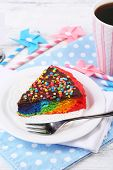 Delicious rainbow cake on plate, on table, on light background