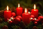 foto of low-light  - Low-key studio shot of a nice advent wreath with baubles and four burning red candles