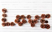 Love word formed with pinecones on wooden background