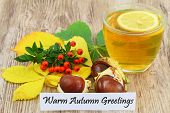 Warm autumn greetings card with cup of lemon tea, rowan berries, chestnuts and autumn leaves on wood