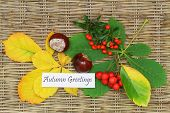 Autumn greetings card with chestnuts, rowan berry and leaves on wicker surface