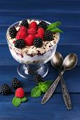 Healthy breakfast - yogurt with  fresh berries and muesli served in glass bowl, on dark color background