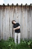 Oblique Standing Teenage Boy In Front Of A Wooden Wall