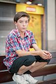 Teenage Boy Crouching On A Bench