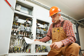 image of electrical engineering  - adult electrician builder engineer worker with electric scheme plan in front of fuse switch board - JPG