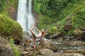 Young woman practicing yoga by the waterfall