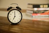 Vintage alarm clock on rustic wood table. Shows 7 o'clock. Pile of books in the background.