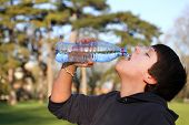 picture of plastic bottle  - A boy thirsty eagerly drinking water from plastic bottle - JPG