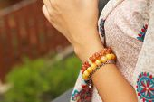 A Young Woman Wearing A Colorful Bracelet.