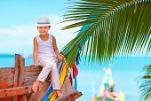 stock photo of life-boat  - cute fashionable boy posing on old boat at tropical beach - JPG