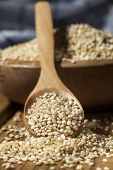 stock photo of quinoa  - Uncooked quinoa in the wooden bowl and spoon on a wooden background - JPG