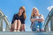 Two girls sitting on metal bridge with blue sky