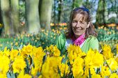 Woman sitting behind daffodils field in park