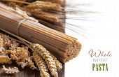 picture of whole-wheat  - Whole wheat italian pasta with wheat spikes on wood - JPG