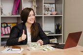 Pretty Teenage Girl Sitting At Desk With A Pile Of Money And Shows Thumb