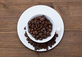 Cup with coffee beans on wood from above