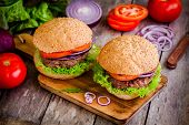 Two Homemade Burgers With Fresh Organic Vegetables On A Rustic Background