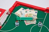 Figures of footbal players on euro banknotes syringe