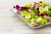 Salad With Herring, Fresh Herbs And Quail Eggs On A  Wooden Background