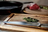 stock photo of lng  - Herbs ready for chopping and kitchen knife lng on a wooden board - JPG