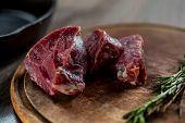 Tenderloin fillet cut into steaks lying on wooden board
