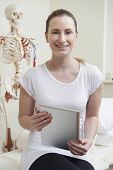 Portrait Of Female Osteopath In Consulting Room With Digital Tablet