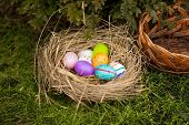 Closeup Shot Of Colored Easter Eggs Lying In Basket On Yard