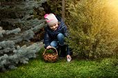 Smiling Girl Taking Easter Egg Form Under The Bush A Backyard
