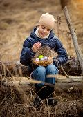 Smiling Girl Sitting On Tree Log At Forest With Easter Basket