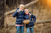 Smiling Girls Posing With Basket Full Of Easter Eggs At Forest