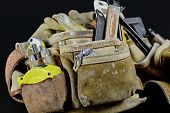 picture of carpenter  - Rugged worn carpenters leather work bags and belt with construction tools and hammer isolated on black and selective focus on leather texture - JPG