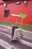 stock photo of cobblestone  - Cleaning trolley with brooms and bin on a cobblestone street - JPG