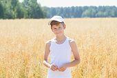 Teenage Farmer Among Common Oat Field