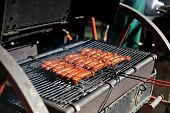 stock photo of frizzle  - tasty meat sausages cooking on hot grill