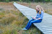 Blonde girl working on tablet computer on wooden path in nature