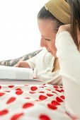 stock photo of vivacious  - Young brunette reading a book or studying comfortably lying on her vivacious red and white polka dot bedspread - JPG